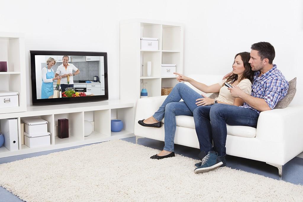 man and woman on couch watching TV 1024x682 - ¿Por qué los nuevos hogares peruanos han reconfigurado el consumo?