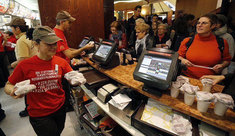 McDonald's staff members serve hamburgers at their fast food restaurant downtown Milan