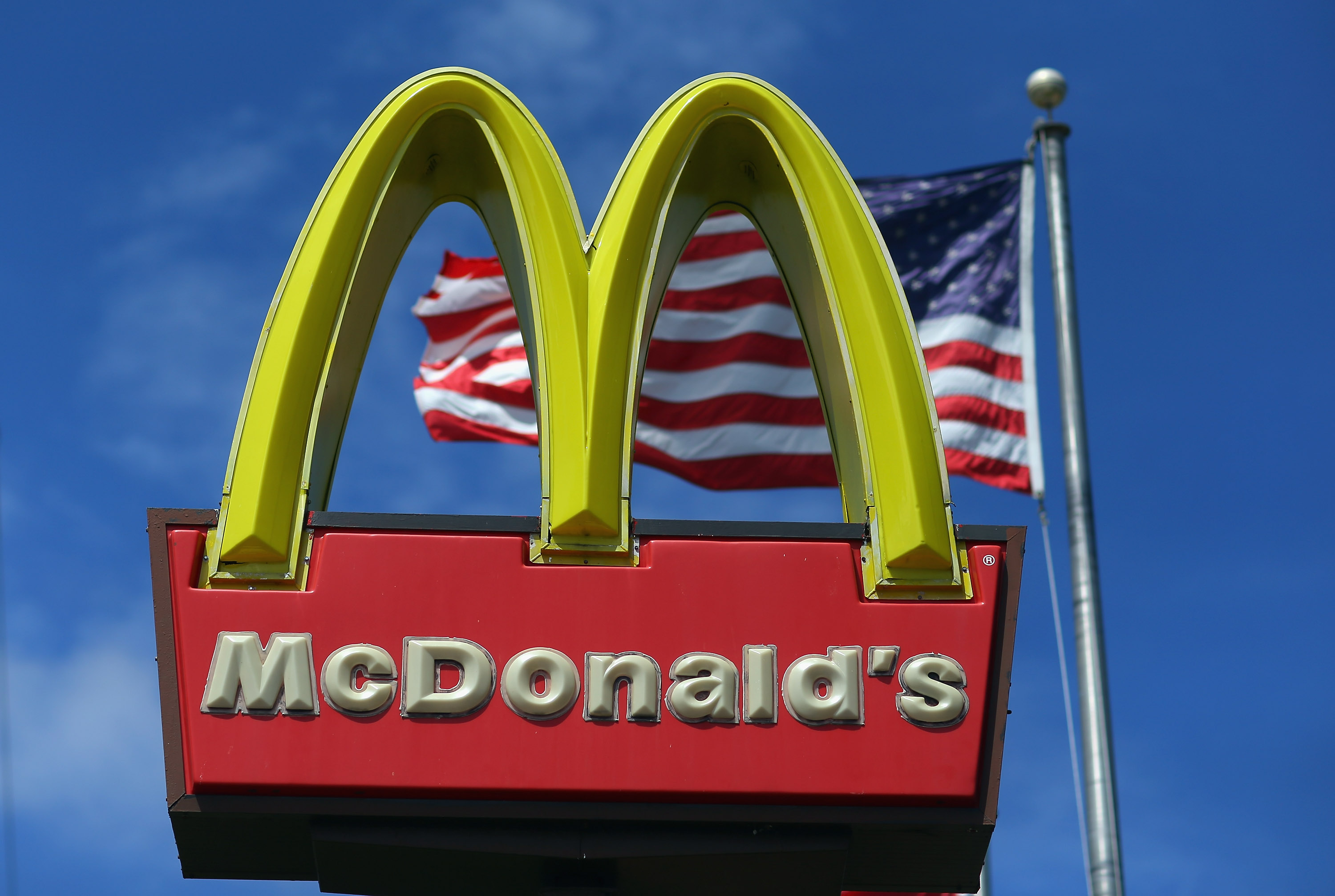 MIAMI, FL - JULY 23:  A sign for a McDonald's restaurant sits in front of an American Flag July 23, 2012 in Miami, Florida. The company announced that 2nd quarter profit dropped 4.5 percent.  (Photo by Joe Raedle/Getty Images)