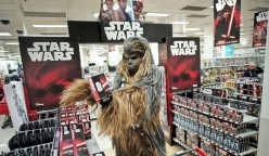 "A fan dressed as Chewbacca selects merchandise from the upcoming film 'Star Wars: The Force Awakens' just before midnight on 'Force Friday' in Sydney, September 4, 2015. New ""Star Wars"" toys and other merchandise were released in stores across Australia and online around the world just after midnight local time.      REUTERS/Jason Reed"